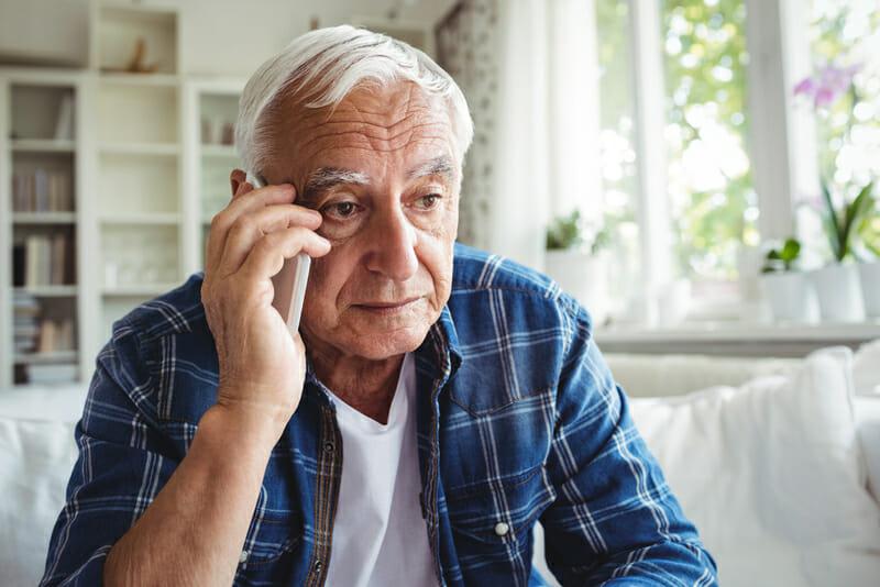 Tensed senior homeowner talking to roofer for roof inspection on mobile phone