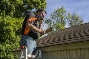 Roofing Contractor On Ladder Figuring Hail Damage Reairs To Roof
